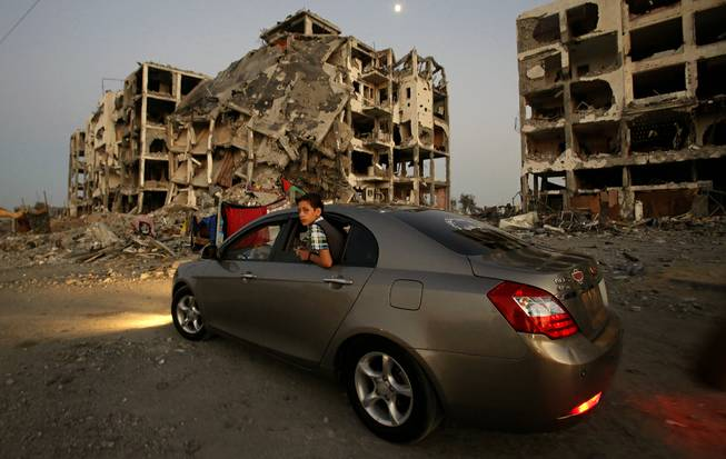 A Palestinian boy surveys the destruction of buildings at a residential neighborhood, in Beit Lahiya, northern Gaza Strip, Thursday, Aug. 7, 2014.