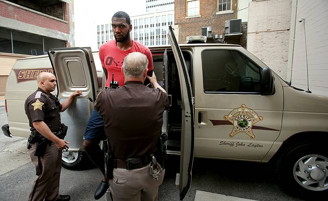 Greg Oden is escorted into the Marion County Community Corrections building, Thursday, Aug. 7, 2014, in Indianapolis. Police arrested former NBA No. 1 draft pick Greg Oden on battery charges early Thursday, alleging that he punched his ex-girlfriend in the face during a fight at his mother's suburban Indianapolis home.