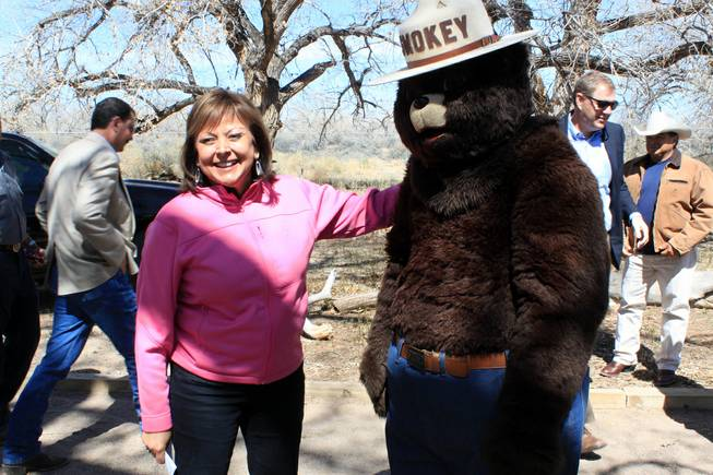 Gov. Susana Martinez prepares to take a photograph with Smokey Bear after a news conference in Albuquerque on Monday, March 31, 2014. Martinez urged residents to be cautious as the state heads into another potentially dangerous fire season.