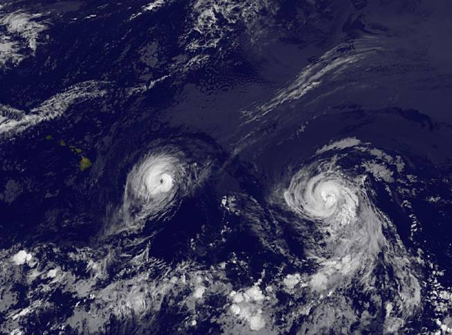 This image provided by NOAA taken Thursday Aug. 7, 2014, at 2 a.m. EDT shows Hurricane Iselle, left and Hurricane Julio.