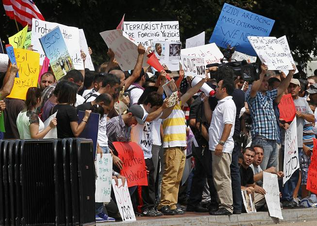 Protesters ask for help for Yazidi people who are stranded by violence in northern Iraq, Thursday, Aug. 7, 2014, across from the White House in Washington.