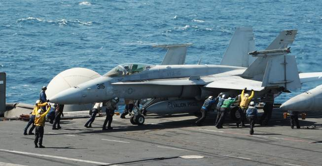 This image released by the U.S. Navy shows sailors guiding an F/A-18C Hornet assigned to the Valions of Strike Fighter Squadron 15 on the flight deck of the aircraft carrier USS George H.W. Bush on Thursday, Aug. 7, 2014, in the Persian Gulf.