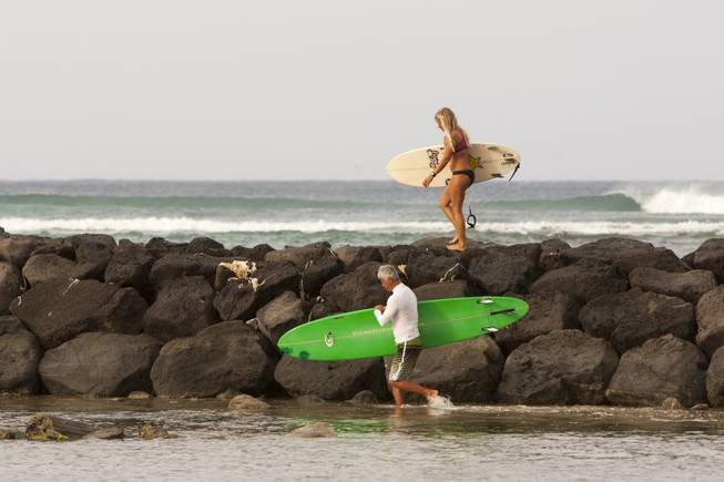 Two surfers head for the waves in Honolulu on Friday, Aug, 8, 2014. High surf is expected in some spots on Oahu due to Tropical Storm Iselle. Iselle came ashore early Friday as a weakened tropical storm, while Hurricane Julio, close behind it, strengthened and is forecasted to pass north of the islands. Iselle is the first tropical storm to hit the state in 22 years.