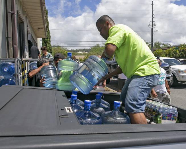Workers at the Menehune Water Company load five gallon bottles of water into a customer's truck, Thursday, Aug. 7, 2014, in Aiea, Hawaii.  Hawaii is bracing for two back to back hurricanes, Iselle and Julio, which are on course to hit the Islands.  Bottles of water are quickly disappearing off shelves in Hawaii causing many people to line up for several hours to purchase water directly from the company.