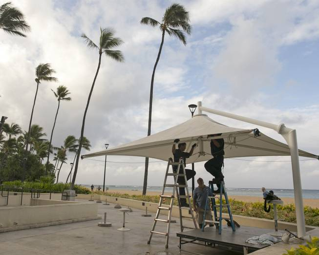 In preparation for heavy winds, workers at the Hale Koa Hotel remove an awning from an outdoor stage in Honolulu on Friday, Aug, 8, 2014. Iselle came ashore early Friday as a weakened tropical storm, while Hurricane Julio, close behind it, strengthened and is forecasted to pass north of the islands. Iselle is the first tropical storm to hit the state in 22 years.