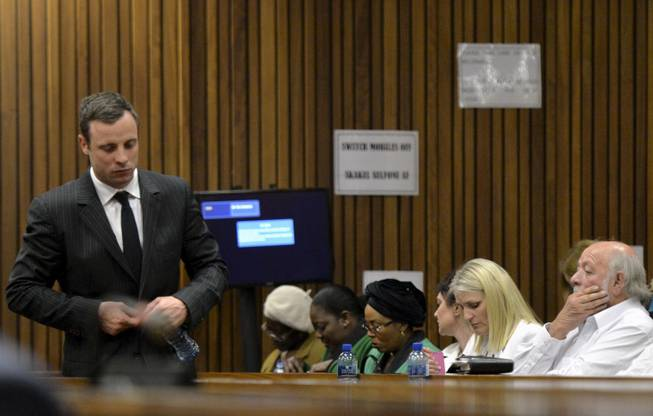 Oscar Pistorius, left, walks past Barry Steenkamp, the father of Reeva Steenkamp, right, during his trial, in Pretoria, South Africa, Friday, Aug. 8, 2014. The chief defense lawyer for Pistorius delivered final arguments in the athlete's trial on Friday, alleging that Pistorius thought he was in danger when he killed girlfriend Reeva Steenkamp and also that police mishandled evidence at the house where the shooting happened.