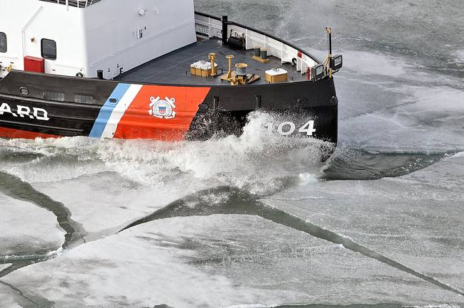 In this Tuesday, April 22, 2014, photo, the 140-foot icebreaker Biscayne Bay cuts through thick ice on the St. Mary's River on its way to escort vessels north to the Soo Locks, in Sault Ste. Marie, Mich. The U.S. Coast Guard spent more than four months breaking ice to open shipping lanes throughout the Great Lakes. Canada has sent two icebreakers to the High Arctic to gather scientific data in support of its plan to bid for control of the sea floor under and beyond the North Pole.