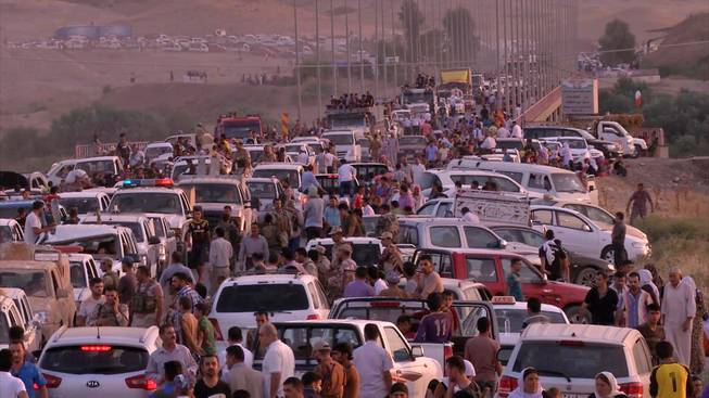 This image made from video taken on Sunday, Aug. 3, 2014, shows Iraqis people from the Yazidi community arriving in Irbil in northern Iraq after Islamic militants attacked the towns of Sinjar and Zunmar. Around 40 thousand people crossed the bridge of Shela in Fishkhabur into the Northern Kurdish Region of Iraq, after being given an ultimatum by Islamic militants to either convert to Islam, pay a security tax, leave their homes, or die.