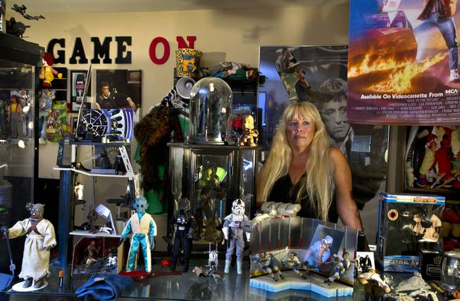 Zita Doyle is surrounded by her husband Cesar Flores' extensive toy collection in their home Friday, Aug. 8, 2014. He was recently killed while riding his bicycle by a driver who has been accused of DUI.