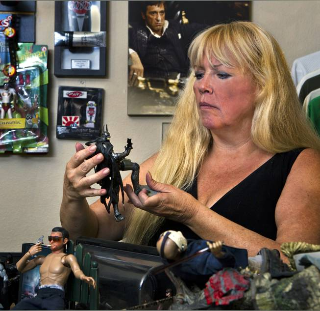 Zita Doyle sorts through a box of action figures from her husband Cesar Flores' extensive toy collection about their home on Friday, August 8, 2014. He was recently killed while riding his bicycle by a driver who has been accused of DUI.