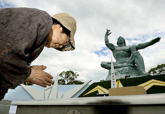 A woman offer a prayer in front of the Statue of Peace at Nagasaki Peace Park in Nagasaki, southern Japan Saturday, Aug. 9, 2014 to mark the 69th anniversary of the world's second atomic bomb attack.