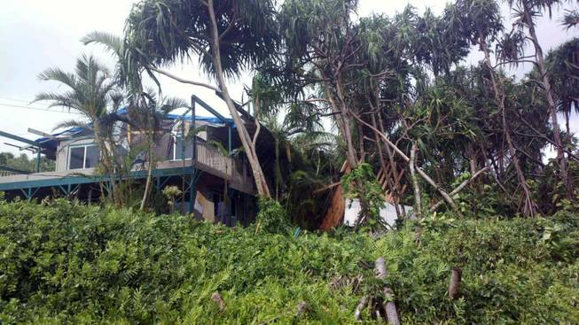 This photo provided by Andrew Fujimura shows the damage from Tropical Storm Iselle on a home in Puna, Hawaii, on Saturday, Aug. 9, 2014. Tropical Storm Iselle, knocked down trees, battered roofs and left the isolated area without electricity.