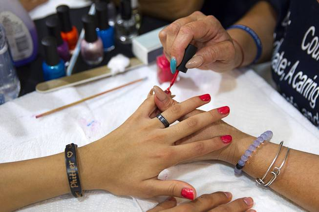 A girl has her nails done during a special back-to-school event for foster children at Square Salon, 1225 South Fort Apache Blvd., during a Sunday, August 10, 2014. The event was sponsored by the CASA Foundation, a local non-profit organization, in partnership with Square Salon and other organizations.