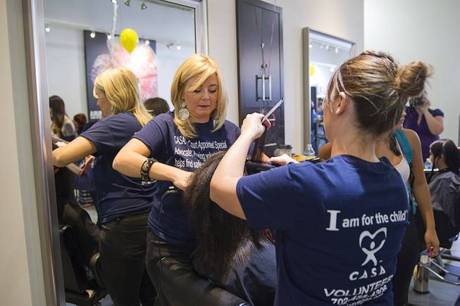 Stylists Laura Stewart, left, and Jodi Lee work on a girl's hair during a special back-to-school event for foster children at Square Salon, 1225 South Fort Apache Blvd., during a Sunday, August 10, 2014. The event was sponsored by the CASA Foundation, a local non-profit organization, in partnership with Square Salon and other organizations.
