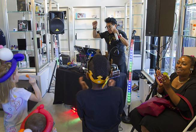 "DJ Miguel plays the ""Chicken Dance"" during a special back-to-school event for foster children at Square Salon, 1225 South Fort Apache Blvd., during a Sunday, August 10, 2014. The event was sponsored by the CASA Foundation, a local non-profit organization, in partnership with Square Salon and other organizations."
