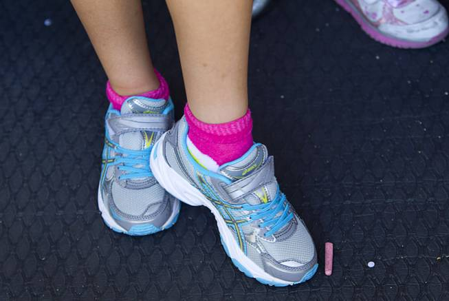 A girl models new shoes, courtesy of Zappos, during a special back-to-school event for foster children at Square Salon, 1225 South Fort Apache Blvd., during a Sunday, August 10, 2014. The event was sponsored by the CASA Foundation, a local non-profit organization, in partnership with Square Salon and other organizations.