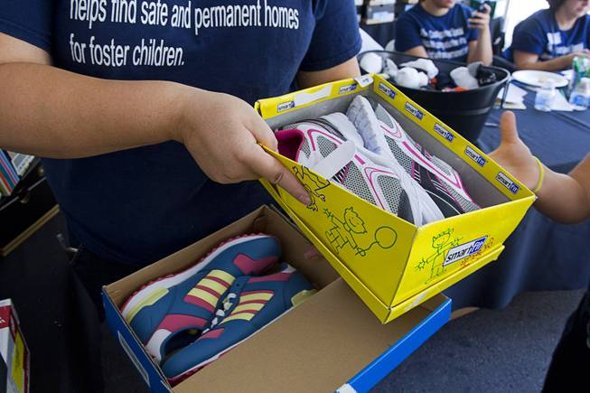 A volunteer hands out shoes, courtesy of Zappos, during a special back-to-school event for foster children at Square Salon, 1225 South Fort Apache Blvd., during a Sunday, August 10, 2014. The event was sponsored by the CASA Foundation, a local non-profit organization, in partnership with Square Salon and other organizations.