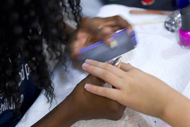 A girl has her nails buffed during a special back-to-school event for foster children at Square Salon, 1225 South Fort Apache Blvd., during a Sunday, August 10, 2014. The event was sponsored by the CASA Foundation, a local non-profit organization, in partnership with Square Salon and other organizations.