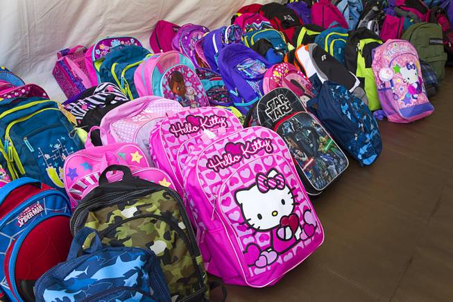 Backpacks are lined up to be given away during a special back-to-school event for foster children at Square Salon, 1225 South Fort Apache Blvd., during a Sunday, August 10, 2014. The event was sponsored by the CASA Foundation, a local non-profit organization, in partnership with Square Salon and other organizations.