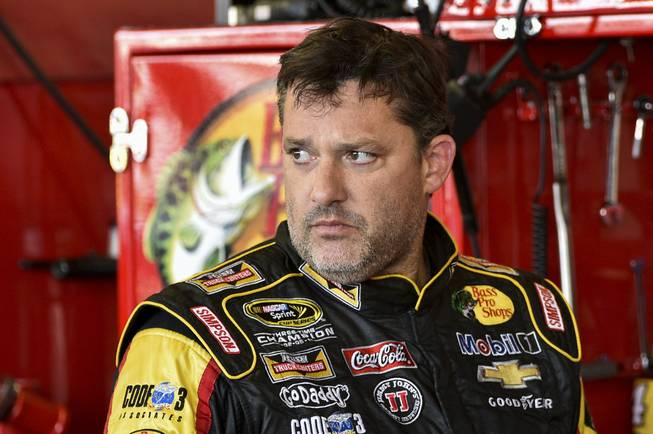 In this Friday, Aug. 8, 2014 photograph, Tony Stewart stands in the garage area after a practice session for Sunday's NASCAR Sprint Cup Series auto race at Watkins Glen International, in Watkins Glen, N.Y.