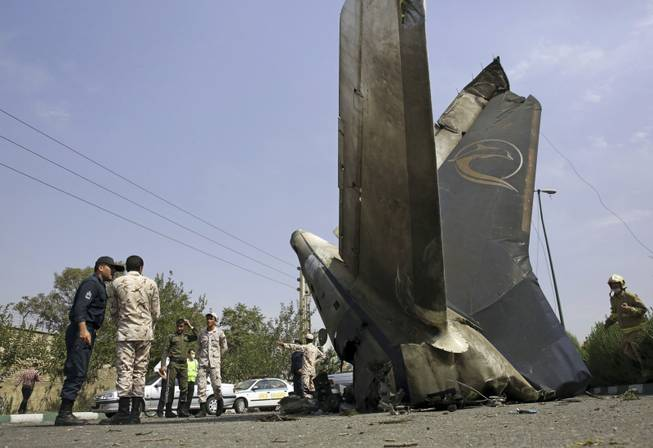 Iranian Revolutionary Guards inspect the site of a passenger plane crash near the capital Tehran, Iran, Sunday, Aug. 10, 2014. An Iranian passenger plane crashed Sunday while taking off from an airport near the capital, Tehran, killing tens of people onboard, state media reported.