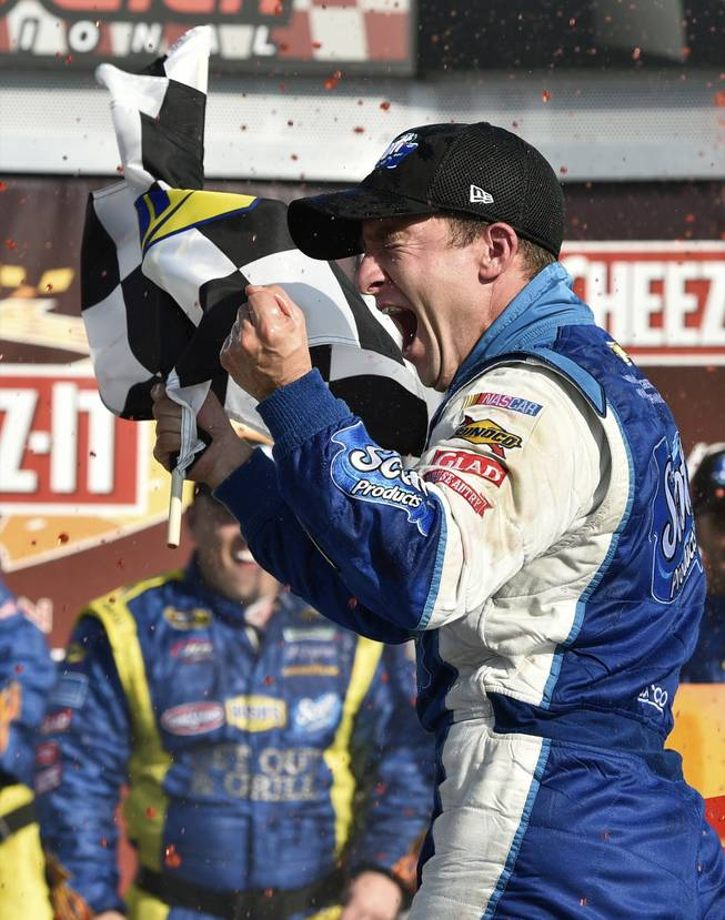 AJ Allmendinger waves the checkered flag as he celebrates in Victory Lane after winning a NASCAR Sprint Cup Series auto race at Watkins Glen International, Sunday, Aug. 10, 2014, in Watkins Glen, N.Y.