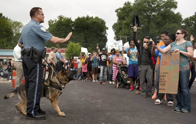 Protestors confront police during an impromptu rally, Sunday, Aug. 10, 2014, to protest the shooting of Michael Brown, 18, by police in Ferguson, Mo. Saturday, Aug. 9, 2014. Brown died following a confrontation with police, according to St. Louis County Police Chief Jon Belmar, who spoke at a news conference Sunday.