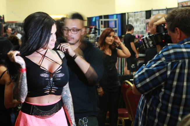 Hew Burney from Top Tattoo Models takes a photo of Heather Moss during the 3rd annual Art-N-Ink Tattoo Festival Saturday, Aug. 9, 2014 at the South Point.