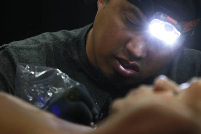 "George ""Keoki"" Davis works an a tattoo at the 3rd annual Art-N-Ink Tattoo Festival Saturday, Aug. 9, 2014 at the South Point."