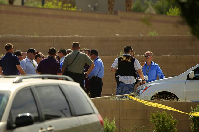 Metro Police investigators gather by the 7600 block of Calico Fields Street after an officer-involved shooting near Fort Apache and Farm roads Monday, Aug. 11, 2014. Police said a suspect was shot after officers responded about 1 p.m. to a disturbance call.