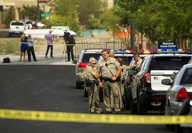 Metro Police are shown in a residential area near Fort Apache and Farm roads after an officer-involved shooting Monday, Aug. 11, 2014. Police said a suspect was shot after officers responded about 1 p.m. to a disturbance call.
