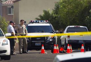 Metro Police investigators stand by the scene of an officer-involved shooting in the 7600 block of Calico Fields Street, near Fort Apache and Farm roads Monday, Aug. 11, 2014. Police said a suspect was shot after officers responded about 1 p.m. to a disturbance call.