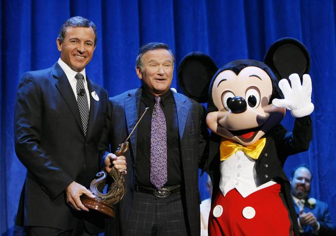 Robert Iger, president and CEO of The Walt Disney Co., Robin Williams and Mickey Mouse at Disneyland on Sept. 10, 2009, in Anaheim. Calif.