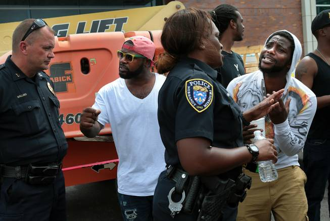 Jamahl Spence, right, pleads his case with a Normandy police officer in front of the Ferguson, Mo. police station on Sunday, Aug. 10, 2014, one day after a Ferguson officer shot and killed Michael Brown.