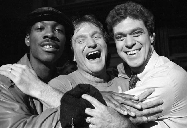 "Robin Williams, center, takes time out from rehearsal at NBC's ""Saturday Night Live"" with cast members Eddie Murphy, left, and Joe Piscopo on Feb. 10, 1984."
