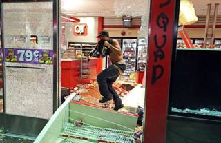 A man jumps through a broken window with bottles of wine in his hands as a QuikTrip store is looted Sunday, Aug. 10, 2014, in Ferguson, Mo. A few thousand people crammed a suburban St. Louis street Sunday night at a vigil for unarmed 18-year-old Michael Brown shot and killed by a police officer, while afterward several car windows were smashed and stores were looted as people carried away armloads of goods as witnessed by an an Associated Press reporter.