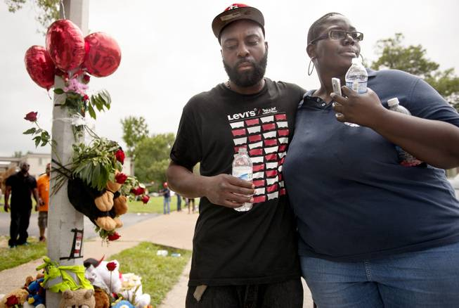 Mourners embrace at a spontaneous memorial for shooting victim Michael Brown, 18, Sunday, Aug. 10, 2014 at the scene of the shooting in Ferguson, Mo. Police said Brown, who was unarmed, was fatally shot Saturday in a scuffle with an officer.
