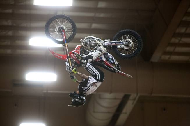A rider performs a trick in the arena during Metal Mulisha freestyle motocross demonstration at the 3rd annual Art-N-Ink Tattoo Festival Friday, Aug. 8, 2014 at the South Point.