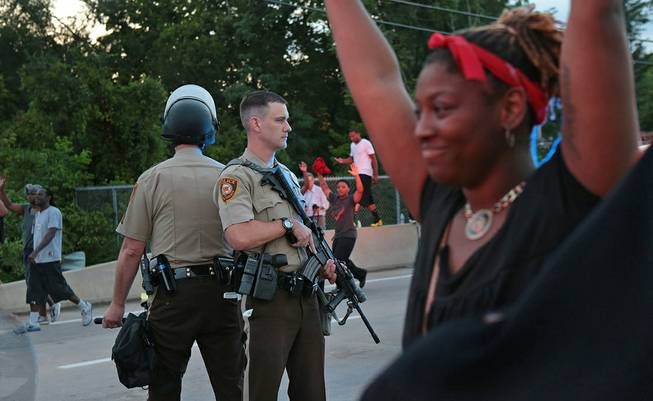 St. Louis County police officers stand back to back as they attempt to move a crowd gathered in front of the QuikTrip, Monday, Aug. 11, 2014, in Ferguson, Mo. Authorities in Ferguson used tear gas and rubber bullets to try to disperse a large crowd Monday night that had gathered at the site of a burned-out convenience store damaged a night earlier, when many businesses in the area were looted.