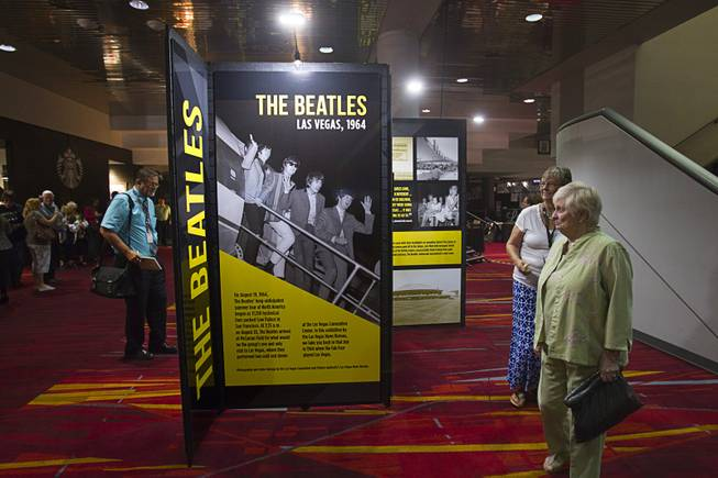 JoAnna Jones, left, and Dorothea Tannenbaum look over a multi-media exhibition during a news conference in the lobby of the Las Vegas Convention Center Tuesday, Aug. 12, 2014. The event celebrated the 50th anniversary of the Beatles concert in Las Vegas on August 20, 1964. The exhibition commemorating the event will be on display in the lobby of the LVCC through Oct. 27.