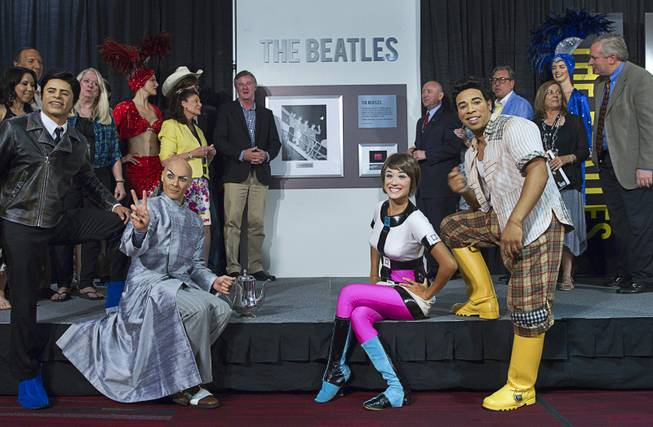 Cirque du Soleil performers from the Love show and others pose in front of a commemorative plaque during a news conference in the lobby of the Las Vegas Convention Center Tuesday, Aug. 12, 2014. The event celebrated the 50th anniversary of the Beatles concert in Las Vegas on August 20, 1964.