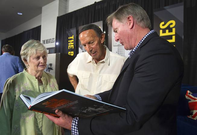 Author Chuck Gunderson shows his book about the Beatles to Bill and Dorothea Tannenbaum during a news conference in the lobby of the Las Vegas Convention Center Tuesday, Aug. 12, 2014. Bill Tannenbaum was an agent who traveled with the Beatles for part of their tour, his wife said. The event celebrated the 50th anniversary of the Beatles concert in Las Vegas on August 20, 1964. A multi-media exhibition commemorating the event will be on display in the lobby of the LVCC through Oct. 27.