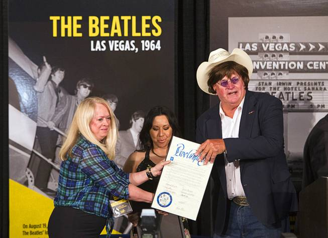 Clark County Commissioner Tom Collins, wearing a Beatles wig and glasses, gives out proclamations to sisters Cheryl, left, and Kim McDonald during a news conference in the lobby of the Las Vegas Convention Center Tuesday, Aug. 12, 2014. Their father Herb McDonald, a Las Vegas publicist, was involved in bringing the Beatles to Las Vegas for a concert in 1964. A multi-media exhibition commemorating the concert will be on display in the lobby of the LVCC through Oct. 27.