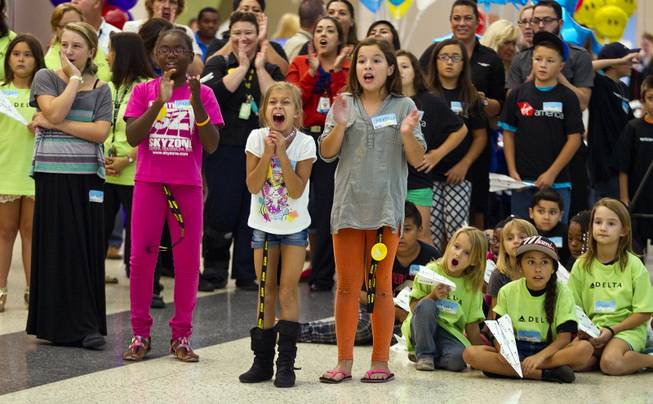 Children from the Boys & Girls Clubs of Southern Nevada cheer for teammates as they throw during the Paper Plane Palooza competition at McCarran International Airport on Tuesday, August 12, 2014.