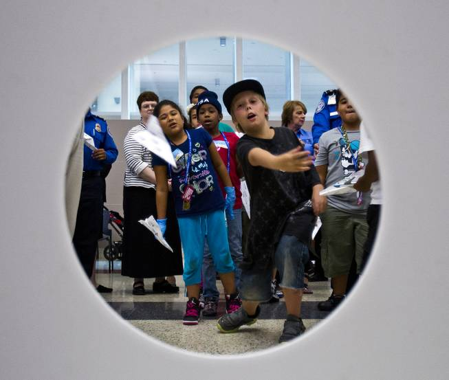 Matthew Moore, 10, with team TSA tosses his airplane towards an open hole in an accuracy competition during Paper Plane Palooza competition at McCarran International Airport on Tuesday, August 12, 2014.