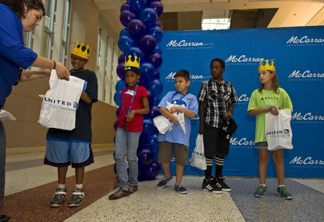Children from the Boys & Girls Clubs of Southern Nevada receive prizes for placing during the Paper Plane Palooza competition at McCarran International Airport on Tuesday, August 12, 2014.