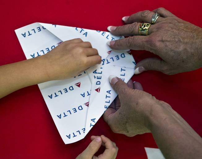 One of many paper airplanes is folded during the Paper Plane Palooza at McCarran International Airport on Tuesday, August 12, 2014.
