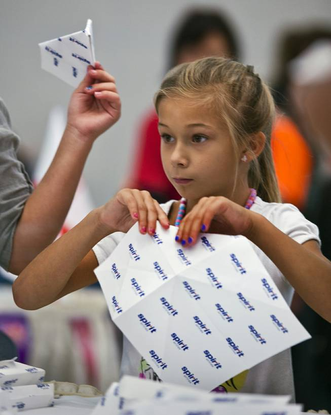 Brooklyn Jimenez, 8, with team Spirit joins others in folding their airplanes before the Paper Plane Palooza competition begins at McCarran International Airport on Tuesday, August 12, 2014.