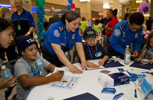 The team from the TSA work together to fold their airplanes before the Paper Plane Palooza competition begins at McCarran International Airport on Tuesday, August 12, 2014.