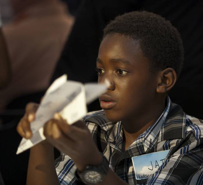 Jai Leveston, 12, with team Hudson News joins others in folding their airplanes before the Paper Plane Palooza competition begins at McCarran International Airport on Tuesday, August 12, 2014.  He would go on to win the long distance throw as a member of the Boys & Girls Clubs of Southern Nevada.